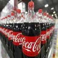 Coke profit falls 28%, but beats expectations