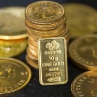 Gold holds losses as dollar gains versus yen