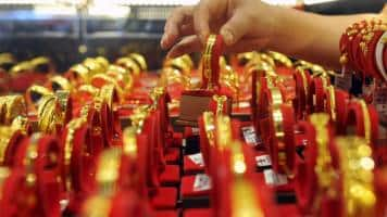 Gold near 3-week low as Fed rate hike expectations boost dollar
