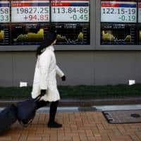 Asian stocks flat, euro slides on French election concerns