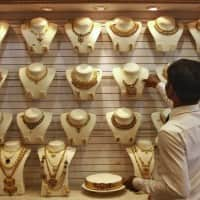 Gold edges down on stronger dollar, but geopolitical tensions support