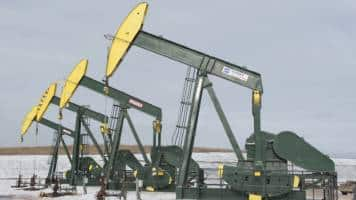 Oil ticks up on weaker dollar, US production outlook caps gains